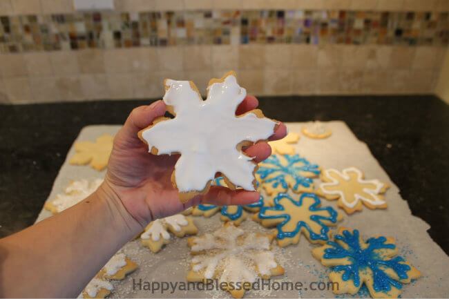 Cover entire surface in icing to create the Snowflake Cookie Recipe and Cookie Decorating Tutorial HappyandBlessedHome.com