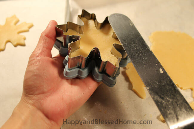 Use spreader to lift cut cookies for the Snowflake Cookie Recipe and Cookie Decorating Tutorial HappyandBlessedHome.com