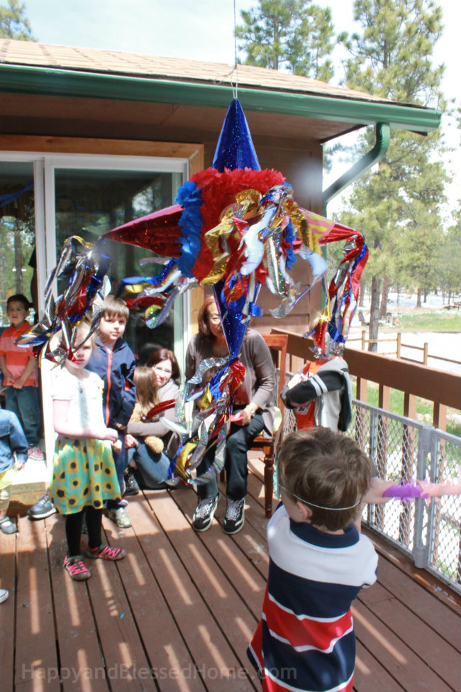 Kids enjoying a Superman Pinata at a Superman Birthday Party fun ideas from HappyandBlessedHome