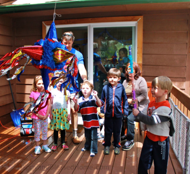 No longer blindfolded Superman Pinata Fun at a Superman Birthday Party from HappyandBlessedHome