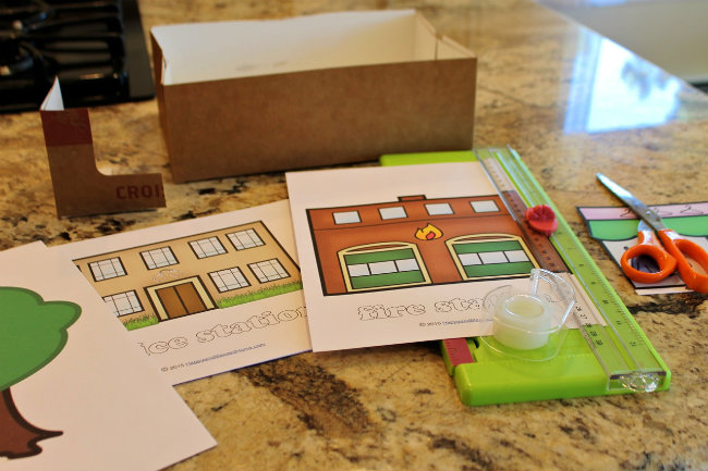 Trim printables to create a town scence and use the corners from a box to prop up buildings - craft tutorial by HappyandBlessedHome