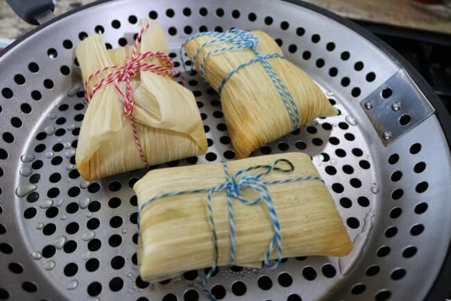 Steam corn wrapped shredded chicken tamales in a steamer for one hour