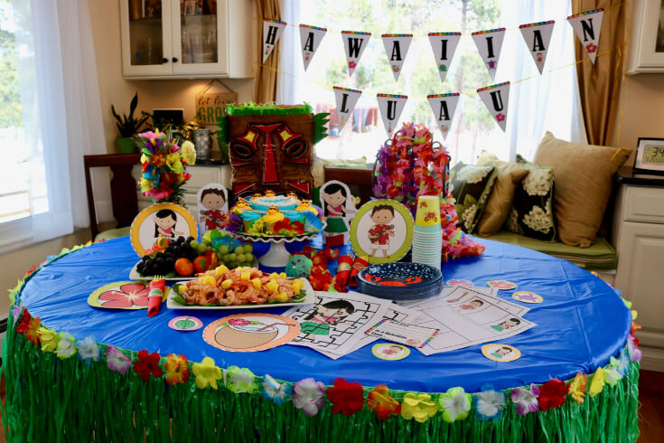 Lay the tablecloth and add the grass skirt first for this Hawaiian Luau Party